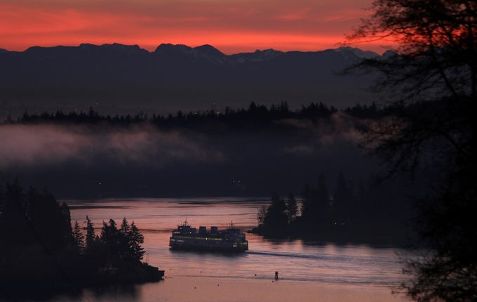 A Bremerton to Seattle, Washington State ferry goes through Rich Passage at sunrise on Saturday, January, 12, 2019.