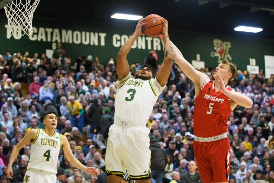 Vermont forward Anthony Lamb (3) leaps to grab the rebound over Hartford's John Carroll (5) during the men's basketball game between the Hartford Hawks and the Vermont Catamounts at Patrick Gym on Saturday night January 12, 2019 in Burlington.