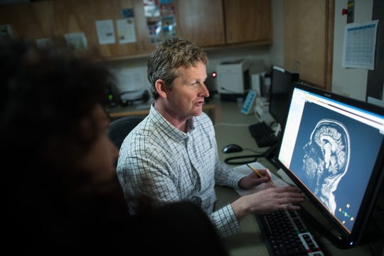 University of Vermont Professor of Psychiatry Hugh Garavan observes a brain scan in an undated university photograph.