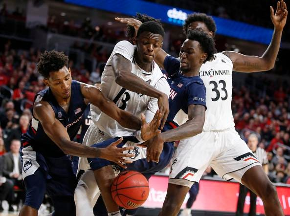 Cincinnati Bearcats forward Tre Scott (13) fights for a rebound with Connecticut Huskies guard Christian Vital, left, and Sidney Wilson, right, during the second half of a basketball game Saturday, Jan. 12, 2019 in Cincinnati. Cincinnati won 74-72 in overtime. (Photo by Gary Landers for the Enquirer)