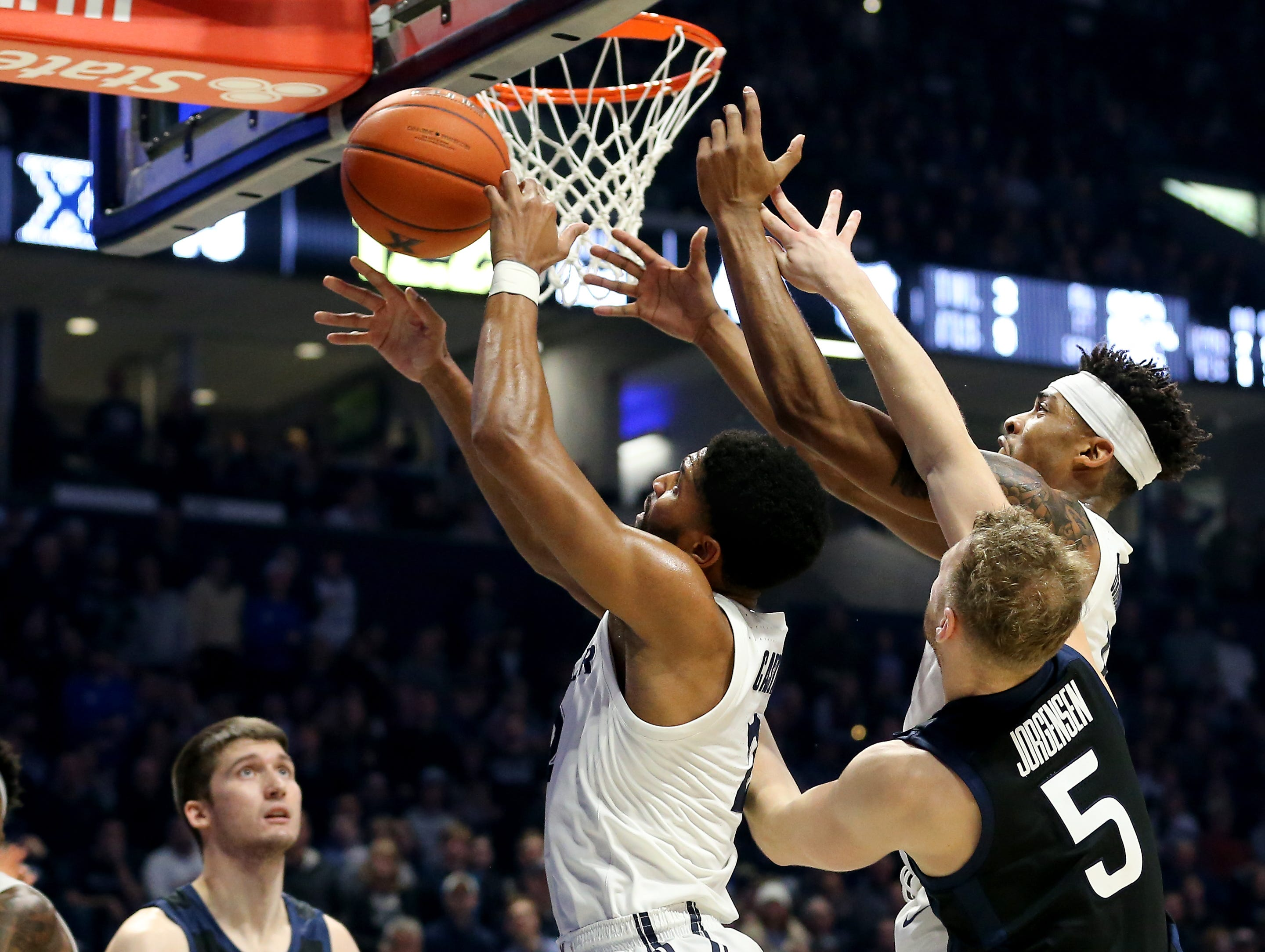 Xavier Musketeers guard Kyle Castlin (2) and Xavier Musketeers guard Paul Scruggs (1) battle for a rebound against Butler Bulldogs guard Paul Jorgensen (5) in the second half of an NCAA college basketball game, Sunday, Jan. 13, 2019, at Cintas Center in Cincinnati. Xavier Musketeers won 70-69.