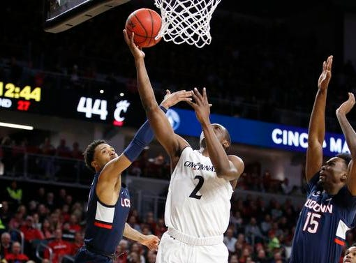 Cincinnati Bearcats guard Keith Williams (2) puts up a shot between Connecticut Huskies guard Jalen Adams (4) and guard Sidney Wilson (15) during the second half of a basketball game Saturday, Jan. 12, 2019 in Cincinnati. Cincinnati won 74-72 in overtime. (Photo by Gary Landers for the Enquirer)