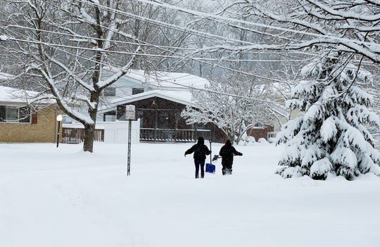 Two women make their way through the snow in their Forest Park neighborhood to shovel a neighbor's driveway Sunday, January 13, 2019. Four inches of snow has fallen in the northern suburbs of Cincinnati, as snow continues to fall.