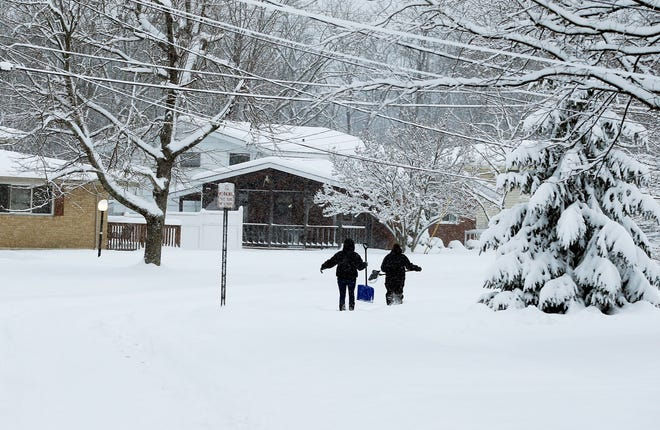Two women make their way through the snow in their Forest Park neighborhood to shovel a neighbor's driveway  Jan. 13, after a snowstorm dumped snow on the northern suburbs of Cincinnatl.