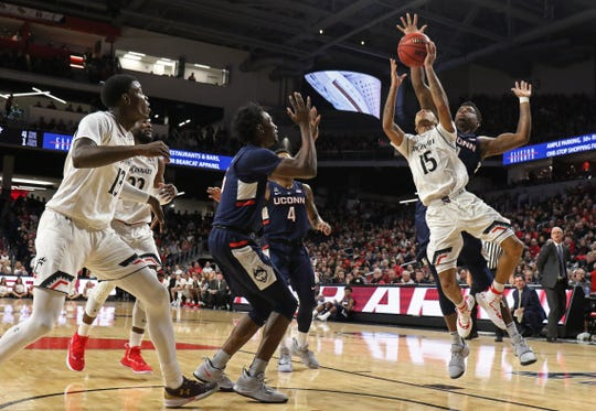 Cincinnati Bearcats guard Cane Broome (15) shoots in front of Connecticut Huskies forward Eric Cobb, rear right, during the first half of a basketball game Saturday, Jan. 12, 2019 in Cincinnati. (Photo by Gary Landers for the Enquirer)