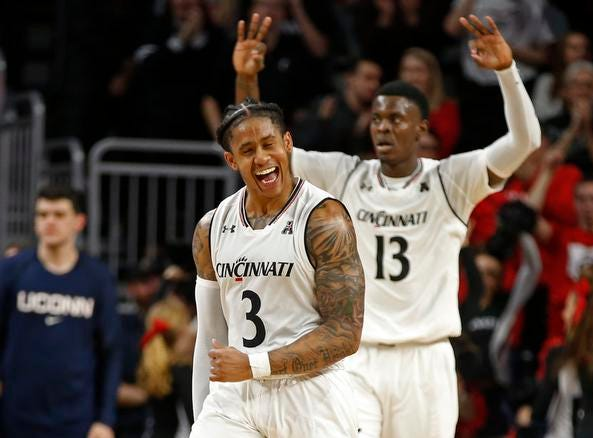 Cincinnati Bearcats guard Justin Jenifer (3) and forward Tre Scott (13) celebrate a Jenifer's three-point shot during overtime of a basketball game Saturday, Jan. 12, 2019 in Cincinnati. Cincinnati won 74-72 in overtime. (Photo by Gary Landers for the Enquirer)