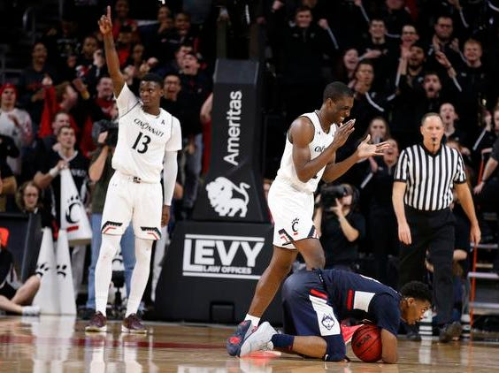 Connecticut Huskies guard Alterique Gilbert, right, reacts to a foul as Cincinnati Bearcats forward Tre Scott (13) and guard Keith Williams (2) celebrate during overtime in a basketball game Saturday, Jan. 12, 2019 in Cincinnati. Cincinnati won 74-72 in overtime. (Photo by Gary Landers for the Enquirer)