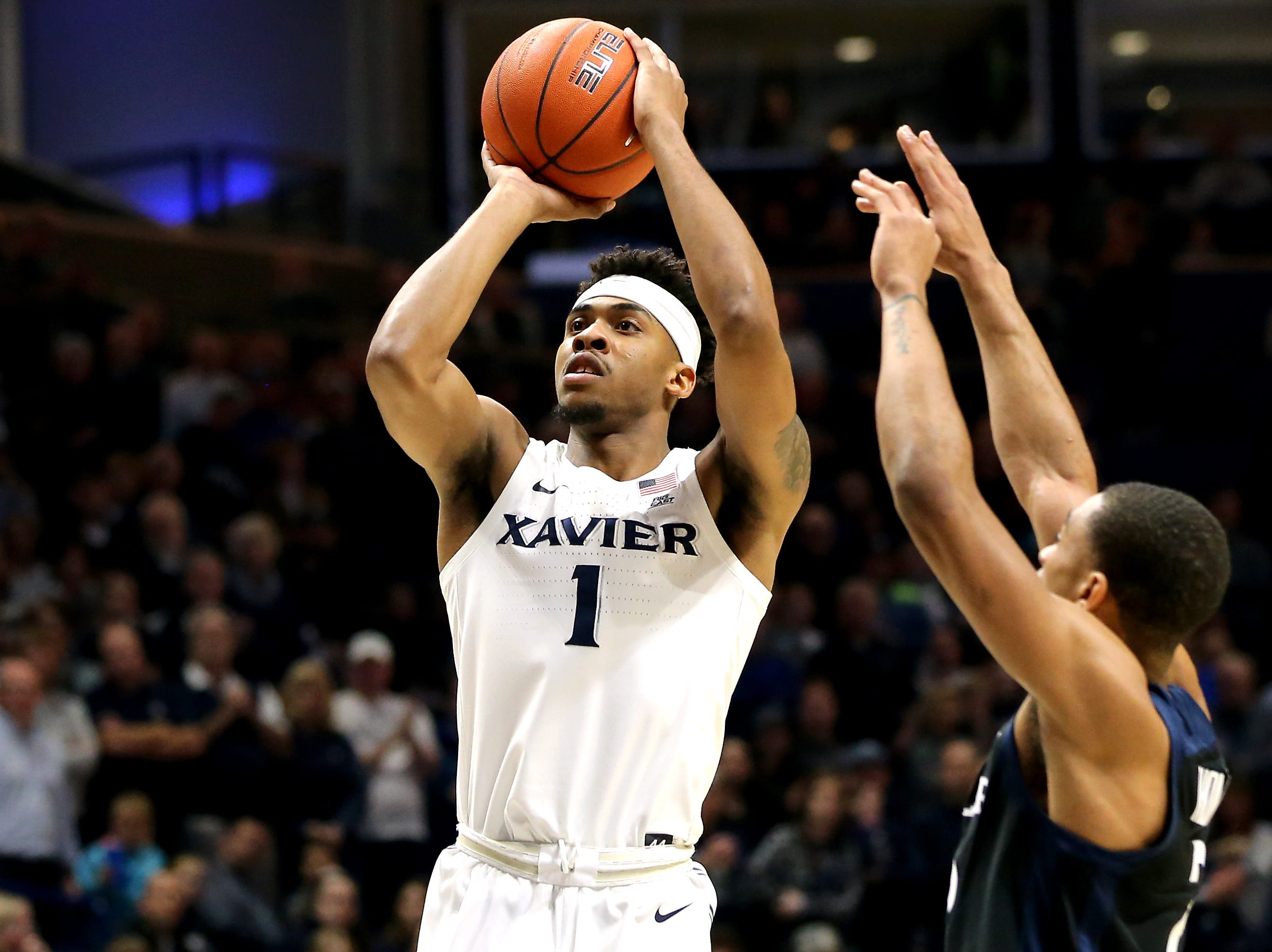 Xavier Musketeers guard Paul Scruggs (1) rises for a shot as Butler Bulldogs guard Aaron Thompson (2) defends in the first half of an NCAA college basketball game, Sunday, Jan. 13, 2019, at Cintas Center in Cincinnati.