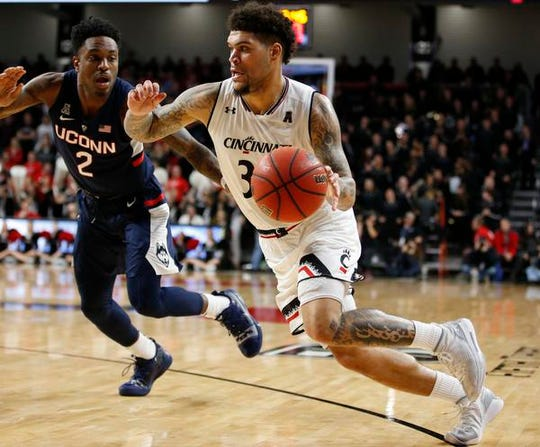 Cincinnati Bearcats guard Jarron Cumberland (34) drives the ball around Connecticut Huskies guard Tarin Smith (2) during the second half of a basketball game Saturday, Jan. 12, 2019 in Cincinnati. Cincinnati won 74-72 in overtime. (Photo by Gary Landers for the Enquirer)