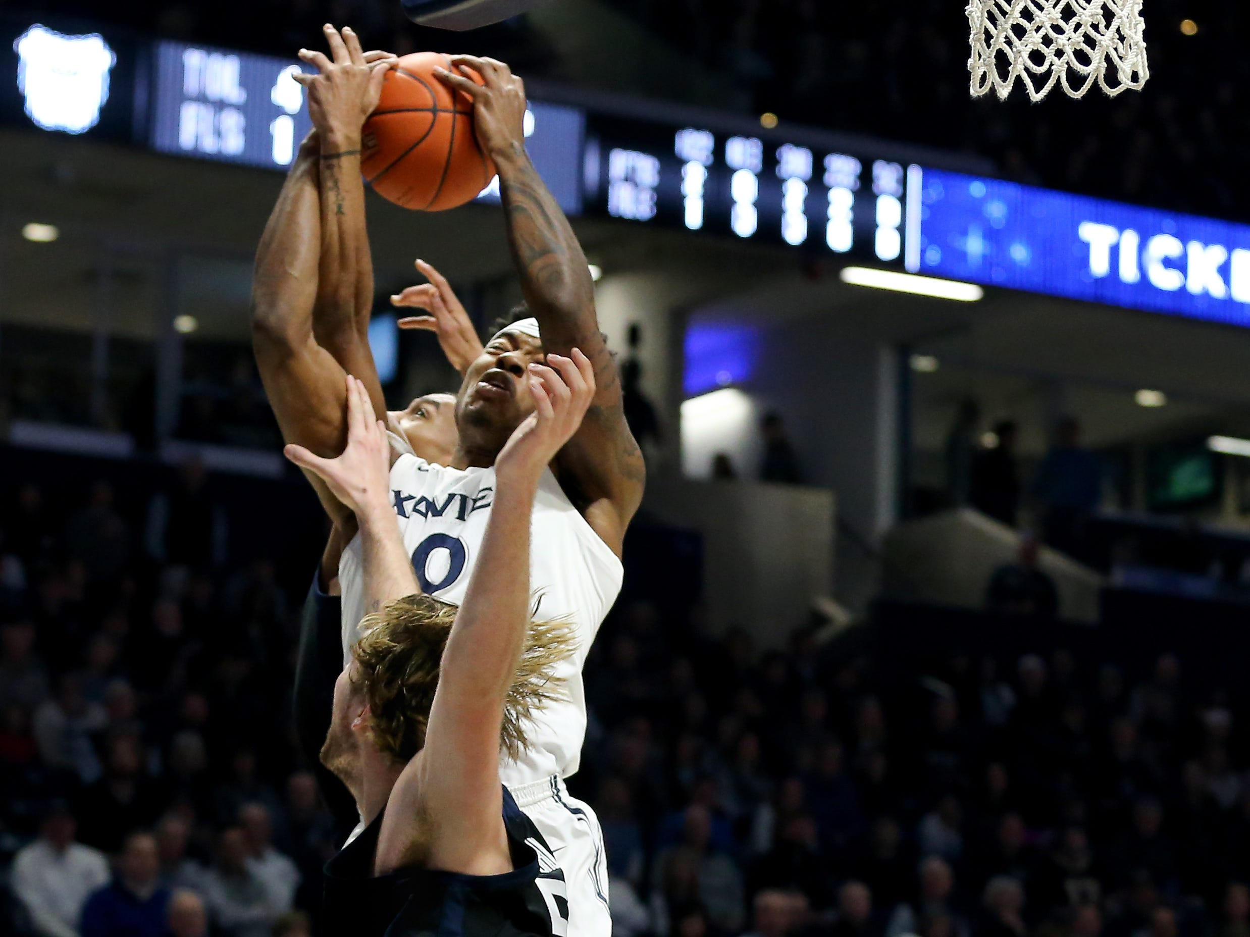 Xavier Musketeers forward Tyrique Jones (0) pulls down a rebound over Butler Bulldogs forward Joey Brunk (50) in the first half of an NCAA college basketball game, Sunday, Jan. 13, 2019, at Cintas Center in Cincinnati.
