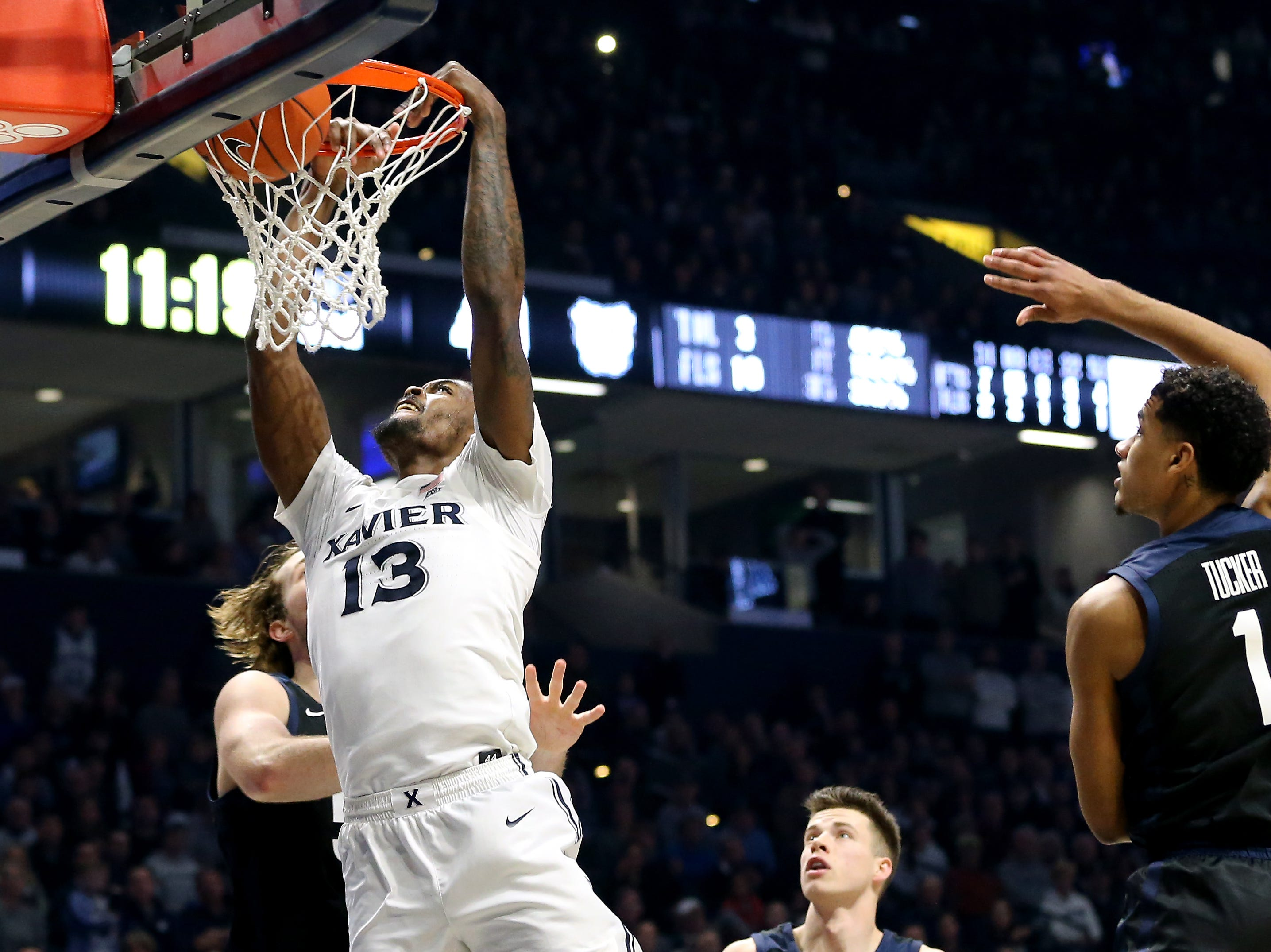 Xavier Musketeers forward Naji Marshall (13) dunks over Butler Bulldogs forward Joey Brunk (50) in the second half of an NCAA college basketball game, Sunday, Jan. 13, 2019, at Cintas Center in Cincinnati. Xavier Musketeers won 70-69.