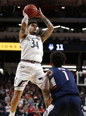 Cincinnati Bearcats guard Jarron Cumberland (34) shoots over Connecticut Huskies guard Christian Vital (1) during the first half of a basketball game Saturday, Jan. 12, 2019 in Cincinnati. (Photo by Gary Landers for the Enquirer)
