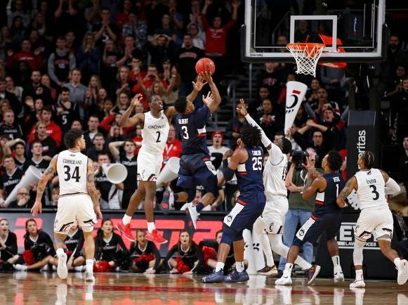 Connecticut Huskies guard Alterique Gilbert (3) puts up the shot to tie the game and send it t overtime against Cincinnati Bearcats guard Keith Williams (2) during the second half of a basketball game Saturday, Jan. 12, 2019 in Cincinnati. Cincinnati won 74-72 in overtime. (Photo by Gary Landers for the Enquirer)