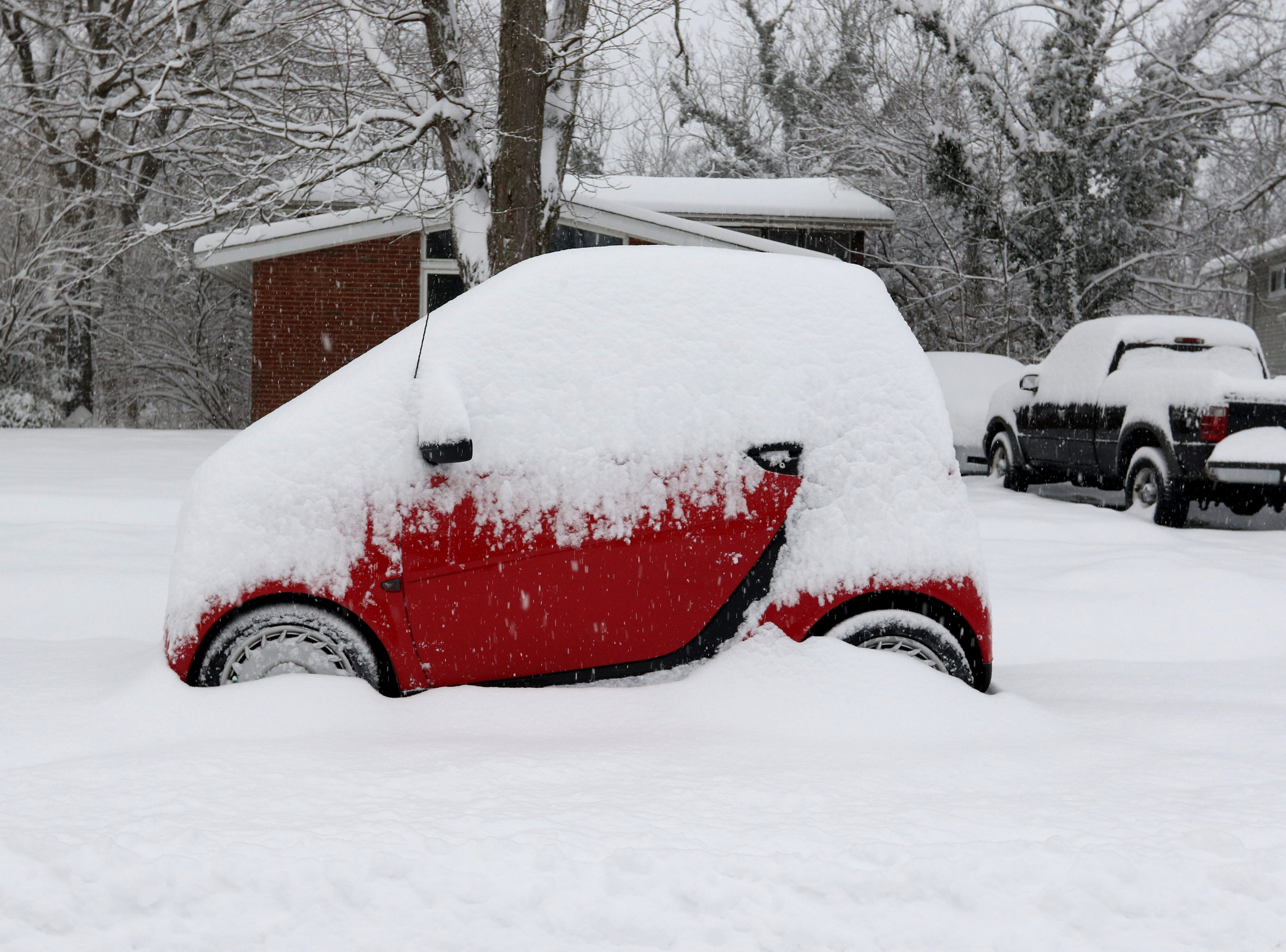 A  Smart car sits snow covered in Forest Park Sunday January 13, 2019.
