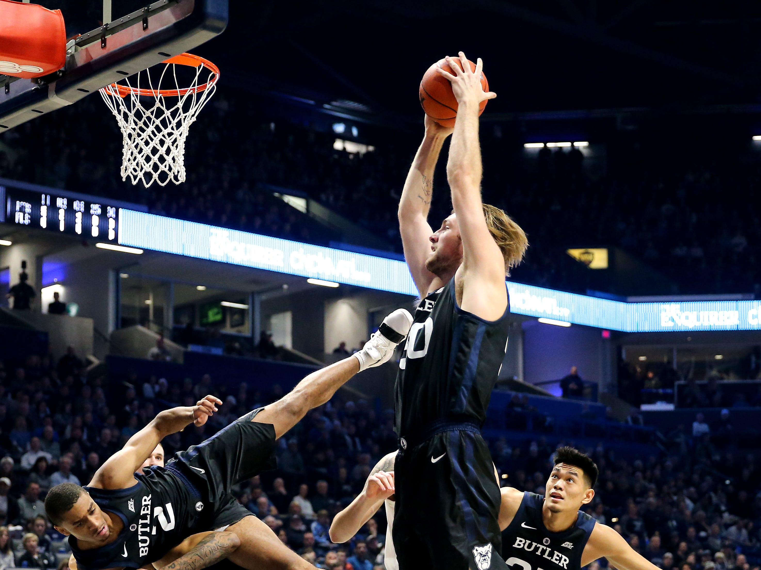 Butler Bulldogs forward Joey Brunk (50) pulls down a rebound as guard Aaron Thompson (2) is upended by teammate forward Jordan Tucker (1), background, in the first half of an NCAA college basketball game, Sunday, Jan. 13, 2019, at Cintas Center in Cincinnati.