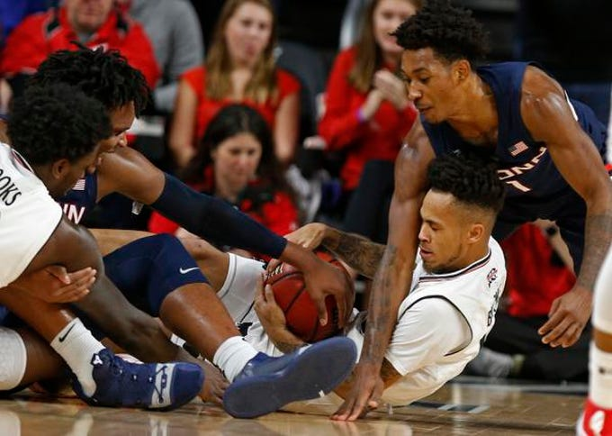 Cincinnati Bearcats guard Cane Broome, center, fight for a loose ball against Connecticut Huskies guard Christian Vital, right, during the first half of a basketball game Saturday, Jan. 12, 2019 in Cincinnati. (Photo by Gary Landers for the Enquirer)