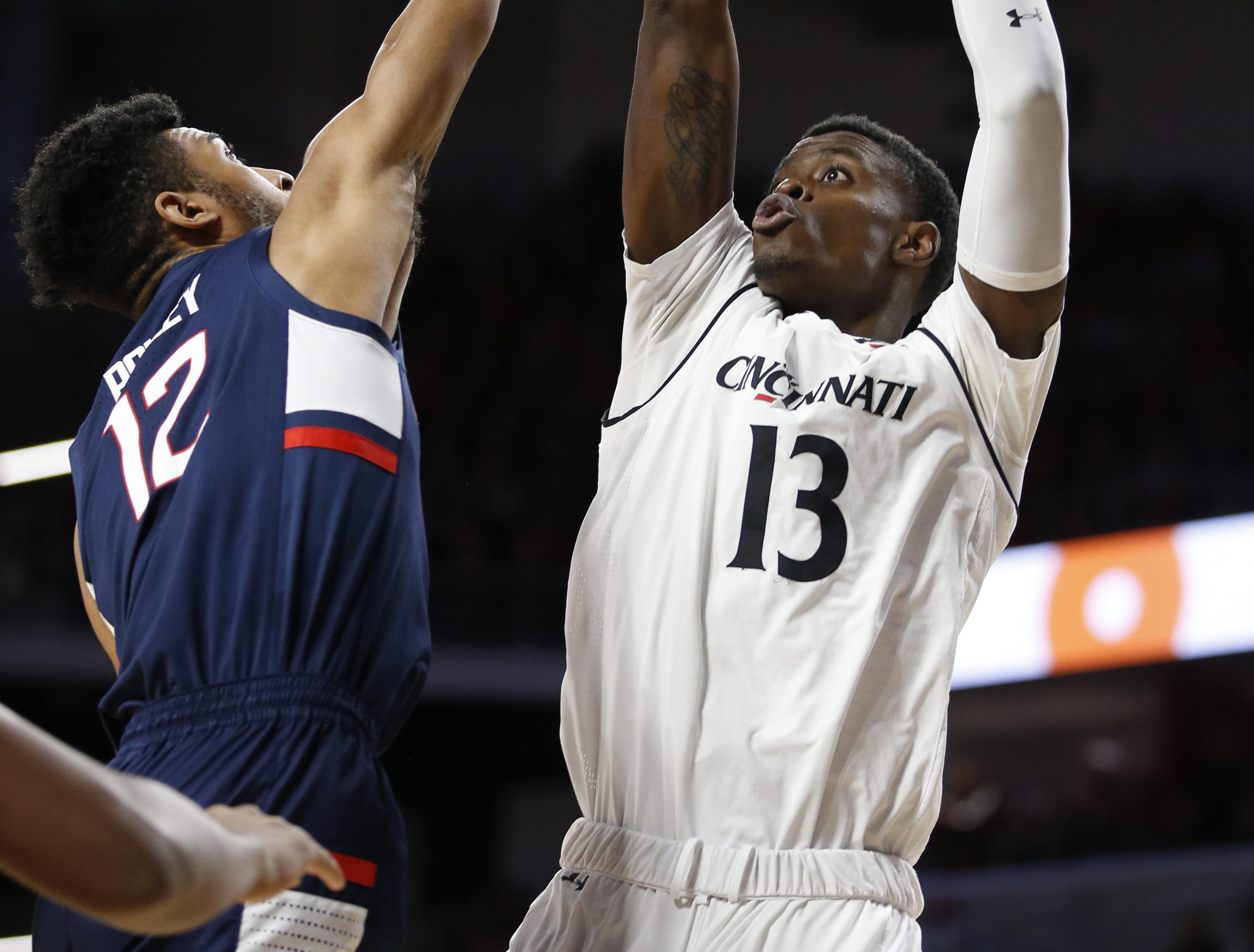 Cincinnati Bearcats forward Tre Scott (13) shoots over Connecticut Huskies forward Tyler Polley (12) during the first half of a basketball game Saturday, Jan. 12, 2019 in Cincinnati. (Photo by Gary Landers for the Enquirer)