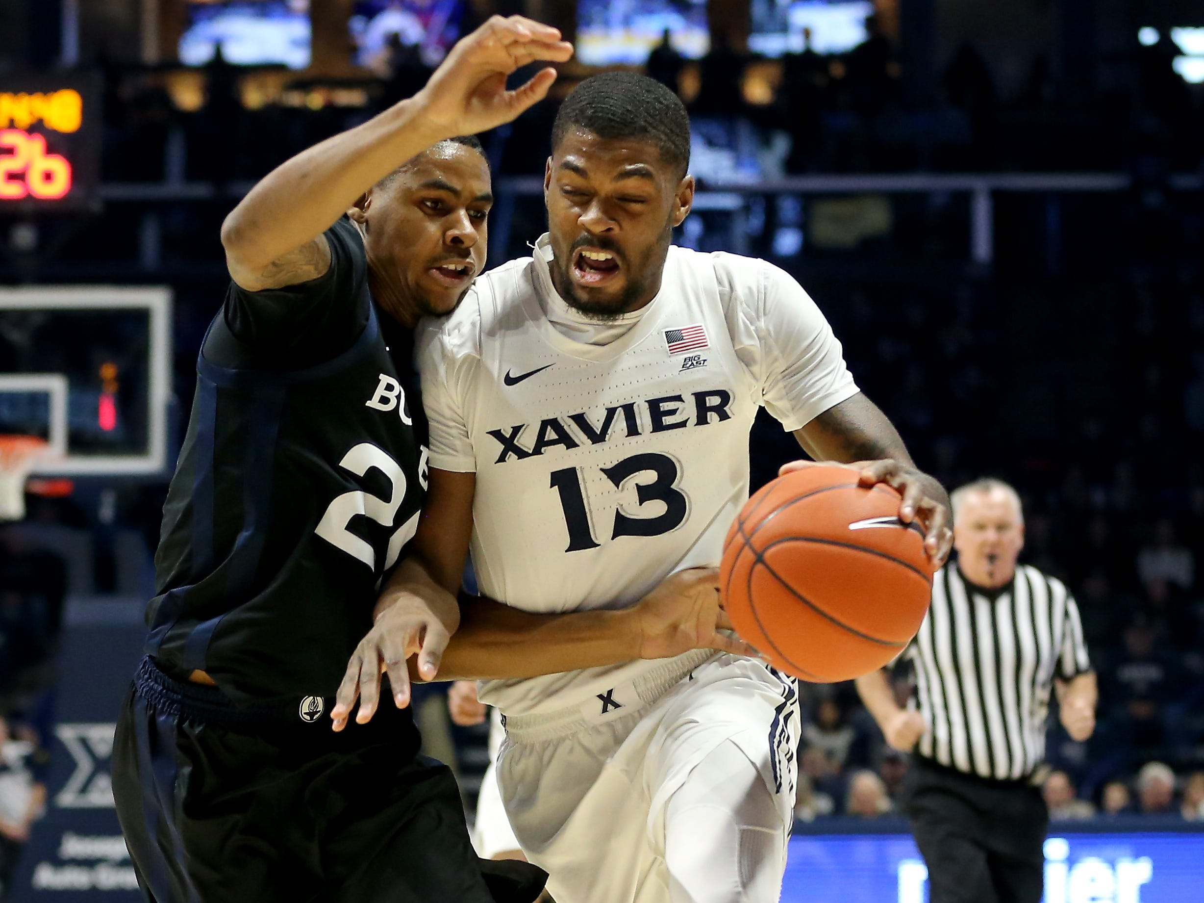 Xavier Musketeers forward Naji Marshall (13) drives to the basket as Butler Bulldogs forward Henry Baddley (20) defends in the first half of an NCAA college basketball game, Sunday, Jan. 13, 2019, at Cintas Center in Cincinnati.