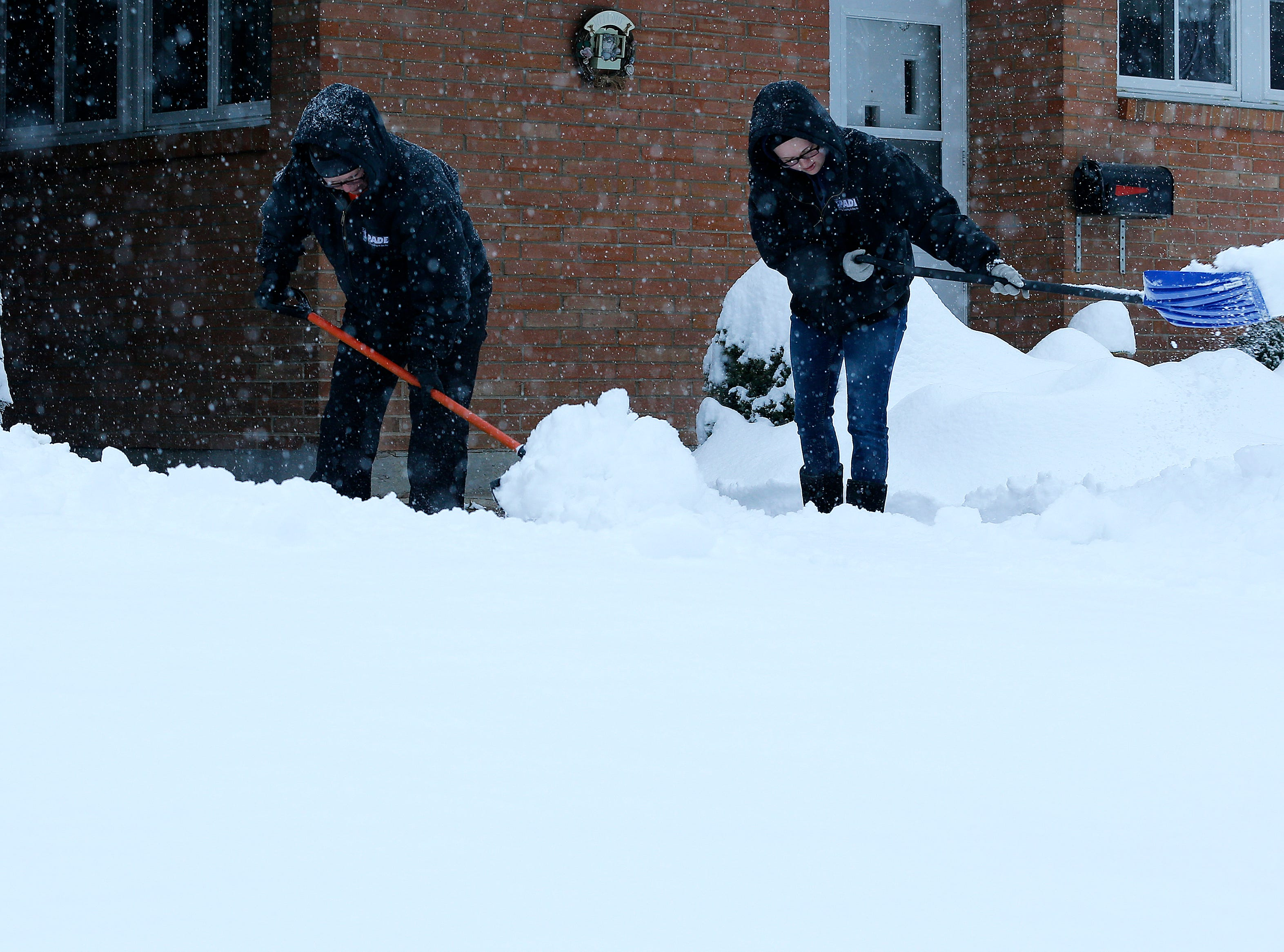 A mother and daughter shovel their neighbor's driveway in Forest Park Sunday January 13, 2019, after more snow dumped overnight.
