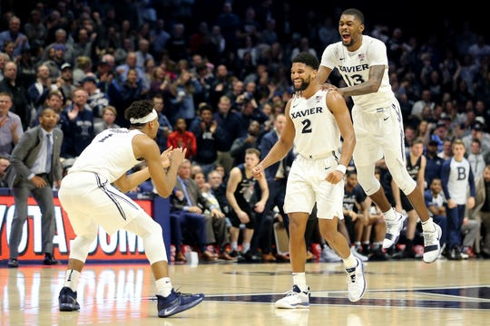 Xavier Musketeers guard Kyle Castlin (2), center, is congratulated by Xavier Musketeers forward Naji Marshall (13), right, and Xavier Musketeers guard Paul Scruggs (1), left, and scoring the game-tying 3-point basket in the second half of an NCAA college basketball game, Sunday, Jan. 13, 2019, at Cintas Center in Cincinnati. Xavier Musketeers won 70-69.