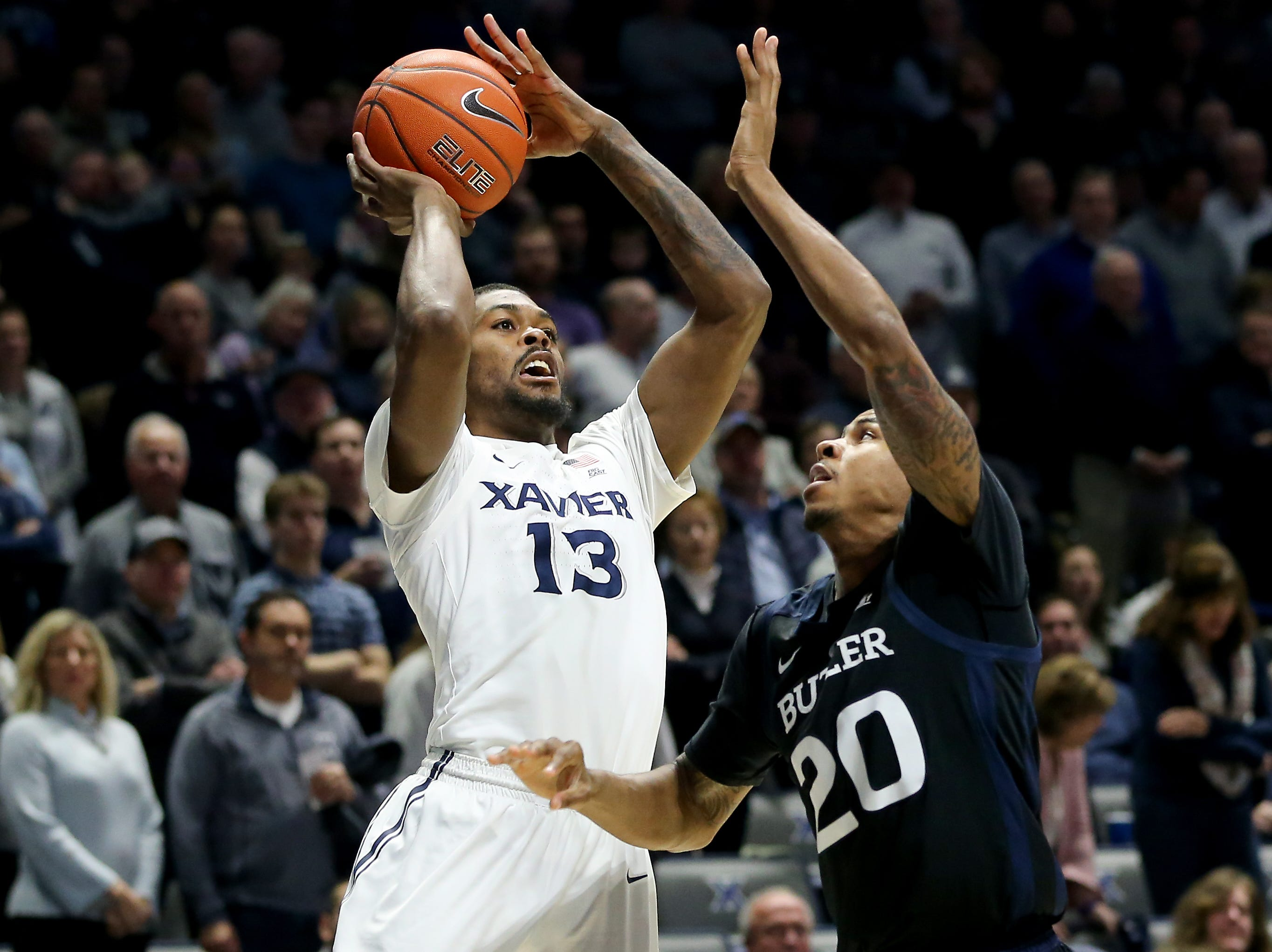 Xavier Musketeers forward Naji Marshall (13) rises for a shot as Butler Bulldogs forward Henry Baddley (20) defends in the first half of an NCAA college basketball game, Sunday, Jan. 13, 2019, at Cintas Center in Cincinnati.