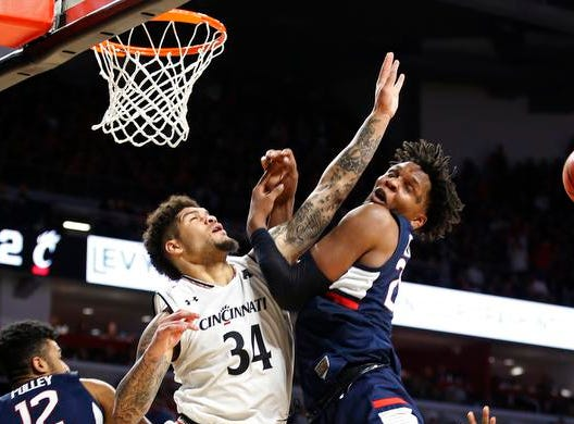 Cincinnati Bearcats guard Jarron Cumberland (34) collides with Connecticut Huskies forward Josh Carlton (25) during the second half of a basketball game Saturday, Jan. 12, 2019 in Cincinnati. Cincinnati won 74-72 in overtime. (Photo by Gary Landers for the Enquirer)