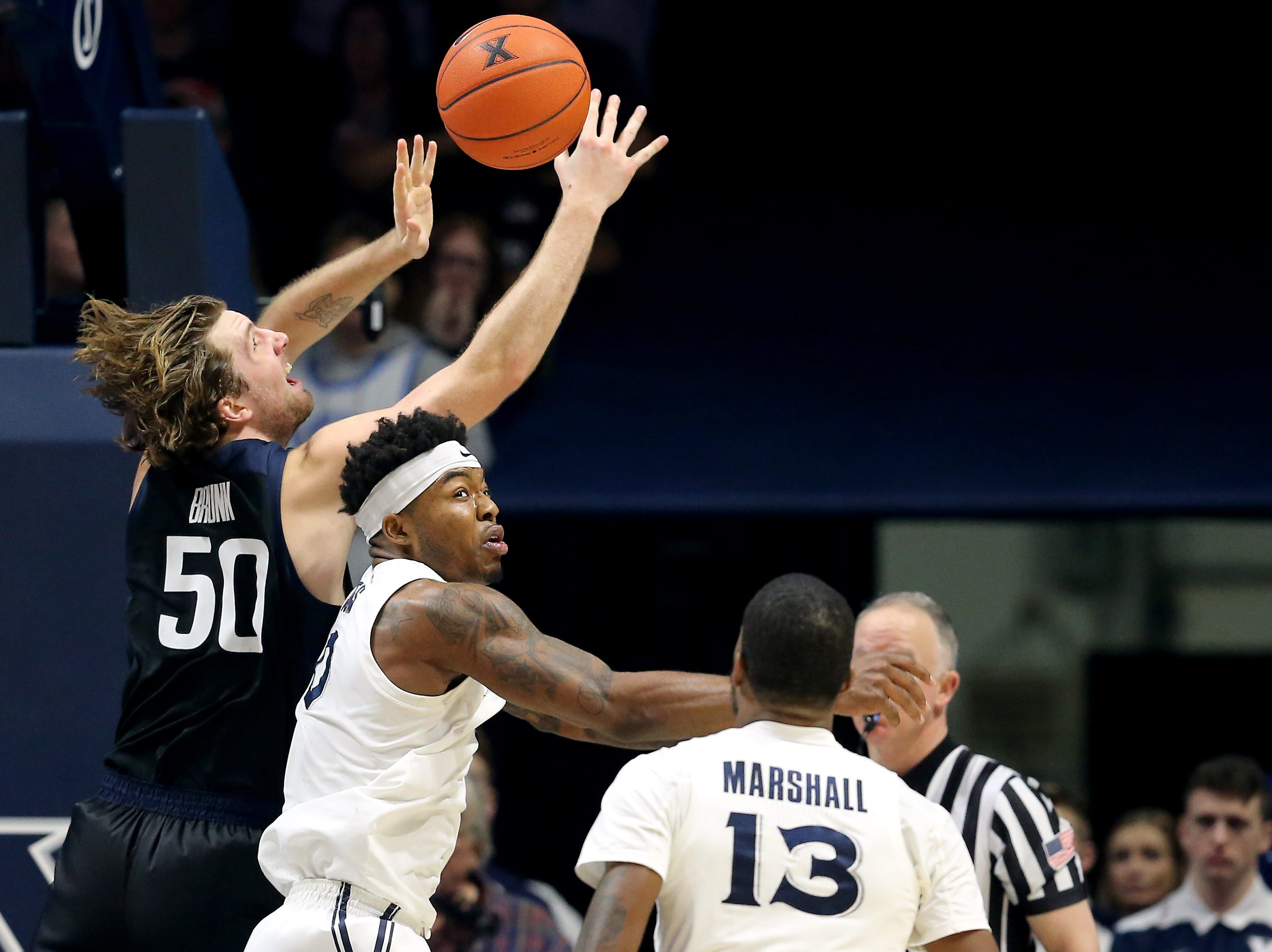 Butler Bulldogs forward Joey Brunk (50) and Xavier Musketeers forward Tyrique Jones (0) fight for a loose ball in the second half of an NCAA college basketball game, Sunday, Jan. 13, 2019, at Cintas Center in Cincinnati. Xavier Musketeers won 70-69.