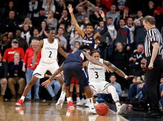 Cincinnati Bearcats guard Justin Jenifer (3) draws a foul from Connecticut Huskies guard Christian Vital (1) with 1.5 seconds on the clock to turn over the ball during overtime of a basketball game Saturday, Jan. 12, 2019 in Cincinnati. Cincinnati won 74-72 in overtime. (Photo by Gary Landers for the Enquirer)