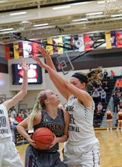 Ankeny senior Sara McCullough (25) runs into the defense of Ankeny Centennial senior Rachel Schon (21) as the Ankeny Hawkettes compete against the Ankeny Centennial Jaguars in high school girls basketball on Friday, Jan. 11, 2019, at Ankeny Centennial High School.