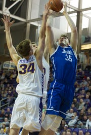 Drake's Nick McGlynn goes up for a shot as University of Northern Iowa's Luke McDonnell and a teammate attempt a block during Sunday afternoon's game.