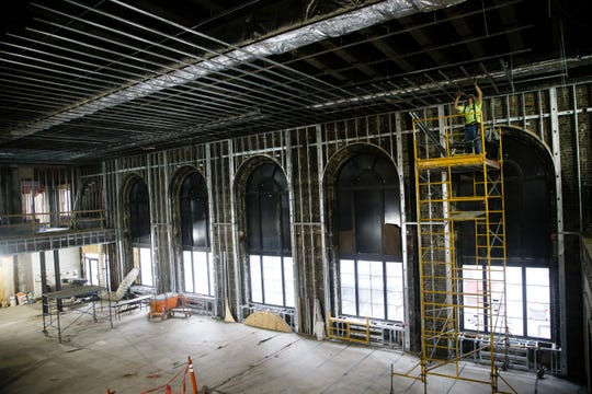 In the two story lobby, a worker installs part of the ceiling at Hotel Fort Des Moines on Friday, Jan. 11, 2019, in Des Moines. As of now, there is no opening date set for the historic hotel which closed at the end of 2015.