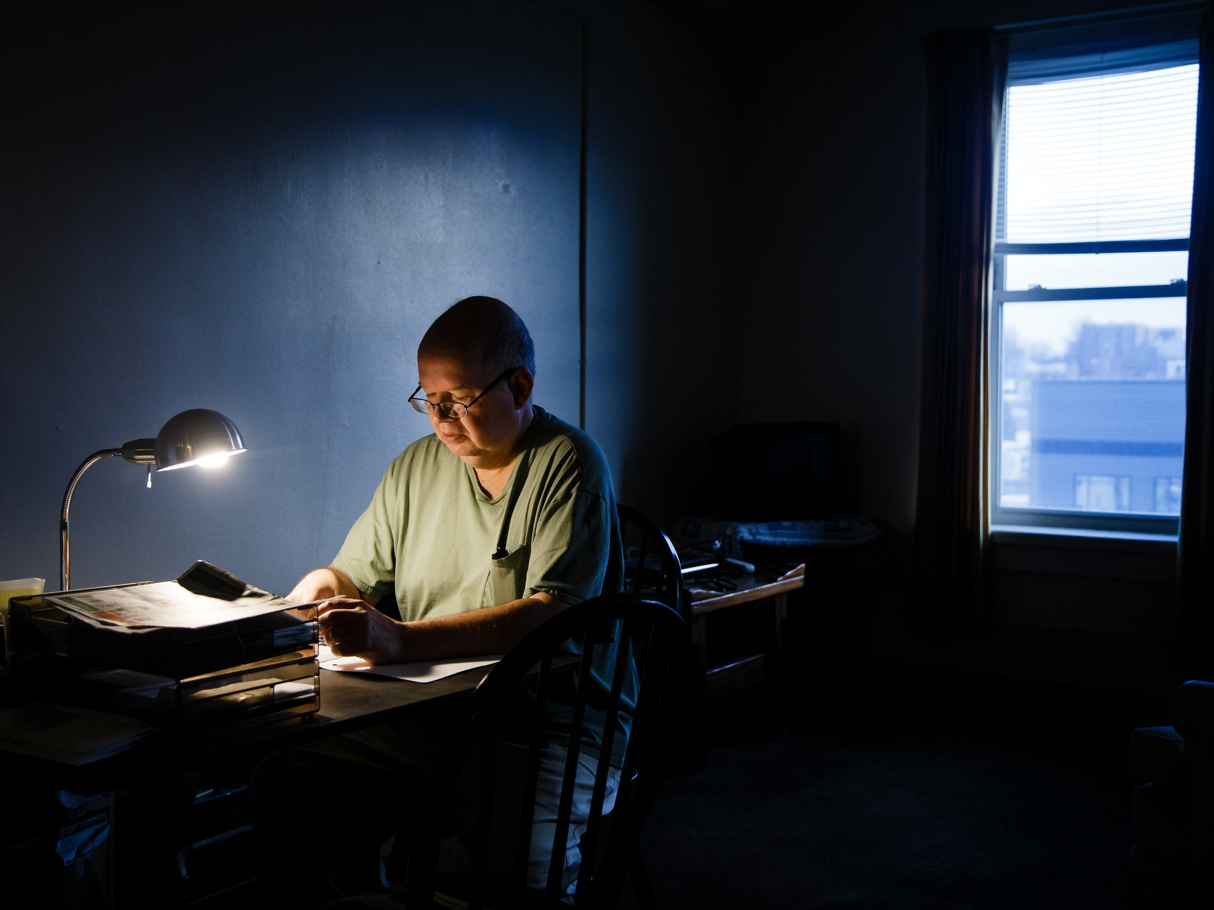 Tom Riordan, 57, sits down to write inside his apartment on Tuesday, Dec. 18, 2018, in Carroll. Riordan has schizophrenia but thanks to St. Anthony's inpatient psychiatric unit he can continue to live on his own and make the short trip there if he needs help coping with his chronic illness.