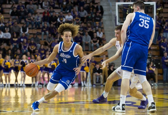 Drake's Noah Thomas dribbles as teammate Nick McGlynn sets a screen on University of Northern Iowa's Spencer Haldeman during Sunday afternoon's game.