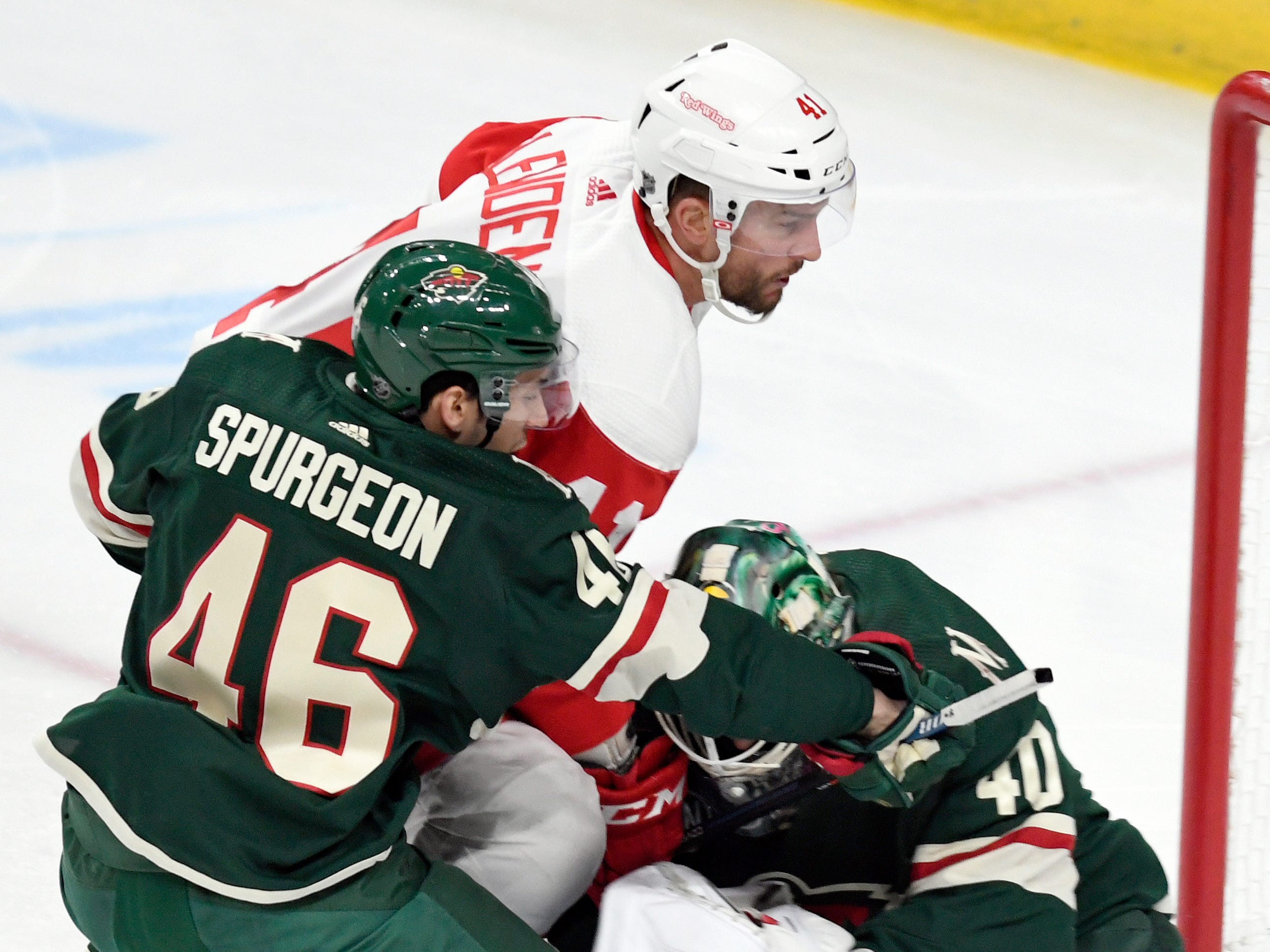 Minnesota Wild's Jared Spurgeon holds off Detroit Red Wings' Luke Glendening as he storms the goal while Wild goalie Devan Dubnyk stops the puck in the first period Saturday, Jan. 12, 2019, in St. Paul, Minn.