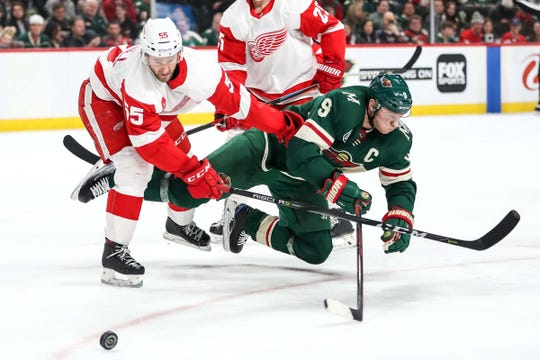 Niklas Kronwall hits Wild forward Mikko Koivu during the Wings' 5-2 win Jan. 12, 2019, in St. Paul, Minn.