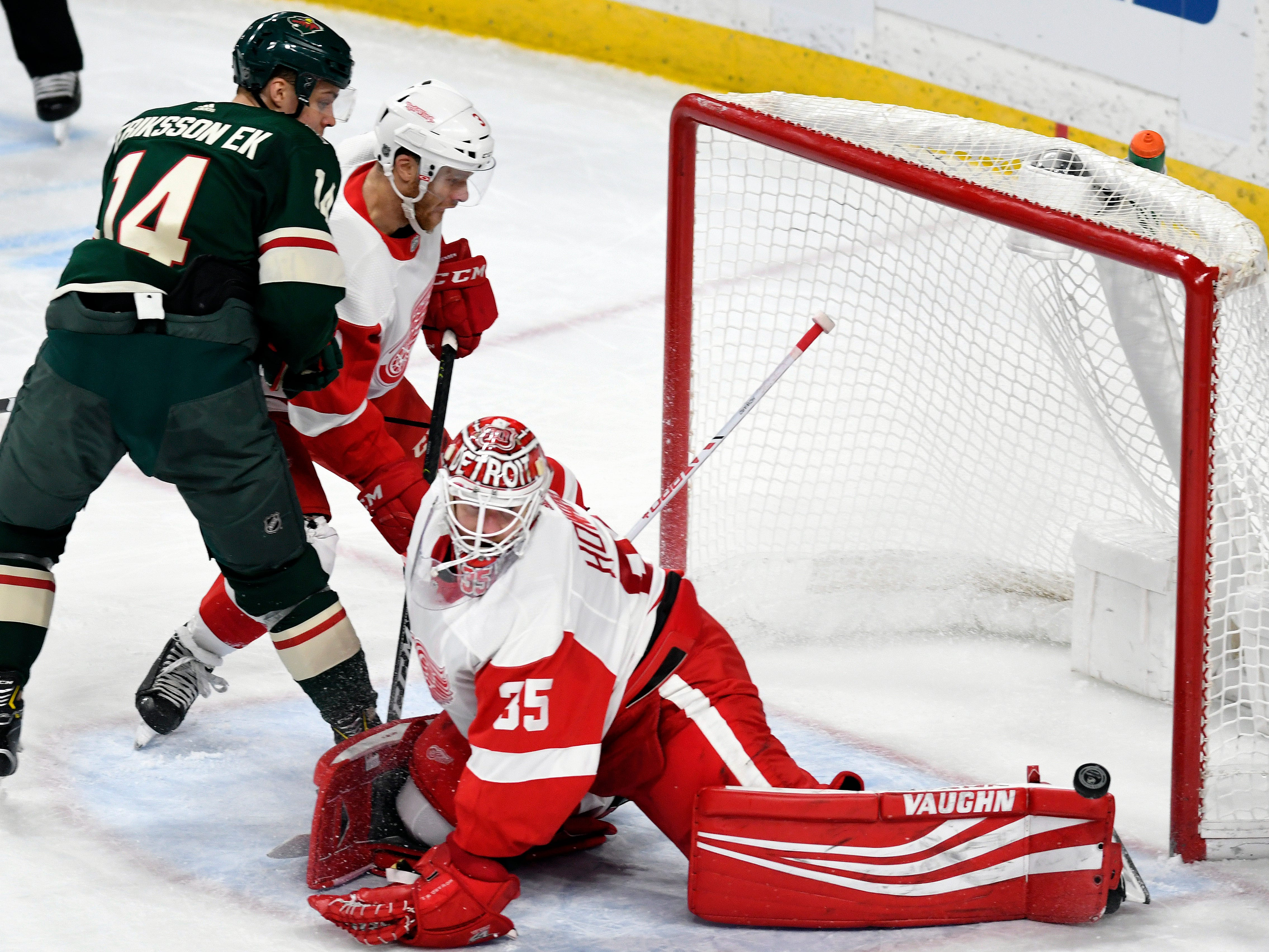 Red Wings goalie Jimmy Howard has the puck roll off the end of his pad as defenseman Nick Jensen, center, holds the Wild's Joel Eriksson Ek away from the goal during the second period of the Wings' 5-2 win on Saturday, Jan. 12, 2019, in St. Paul, Minn.