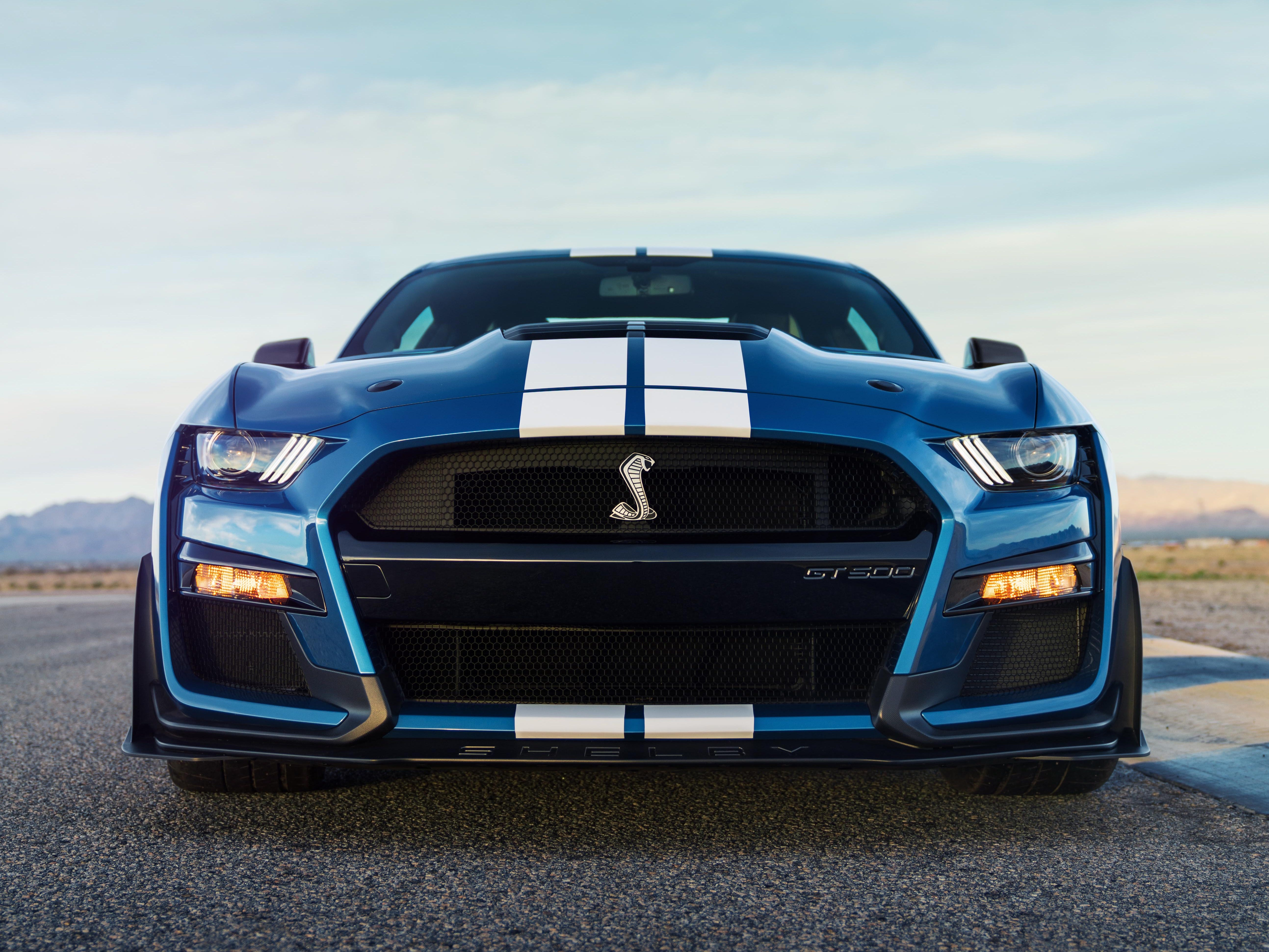 A blue Mustang GT500 sports white racing stripes.