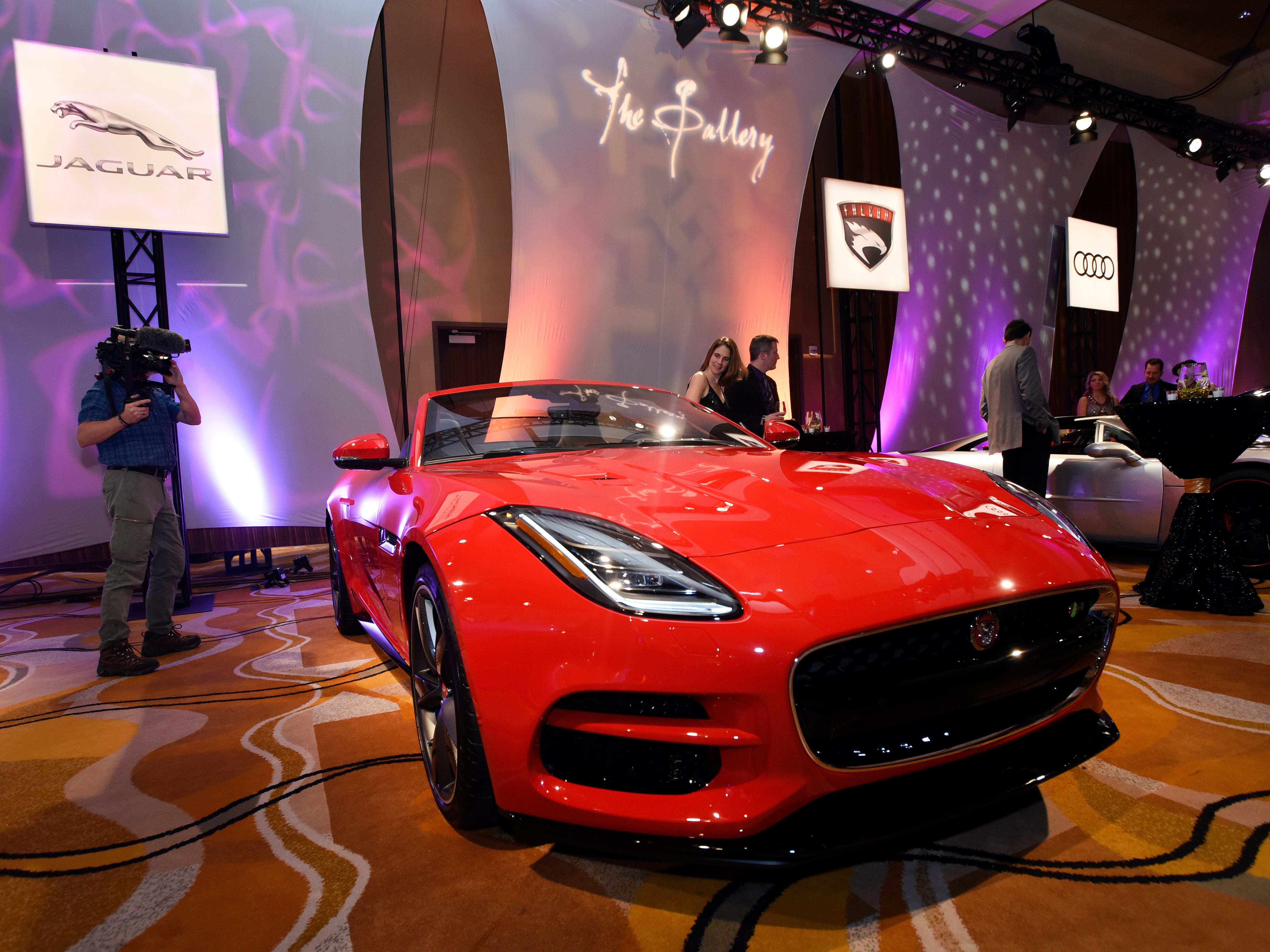 Attendees look over the Jaguar F-type R coupe at The Gallery, held at the MGM Grand Detroit, Saturday night.