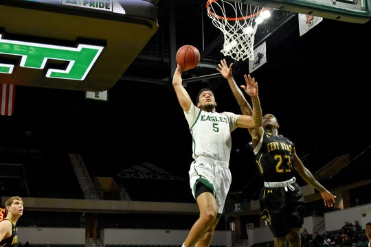 Eastern Michigan's Elijah Minnie goes in for a layup against Kent State's Jaylin Walker Saturday at the Convocation Center.