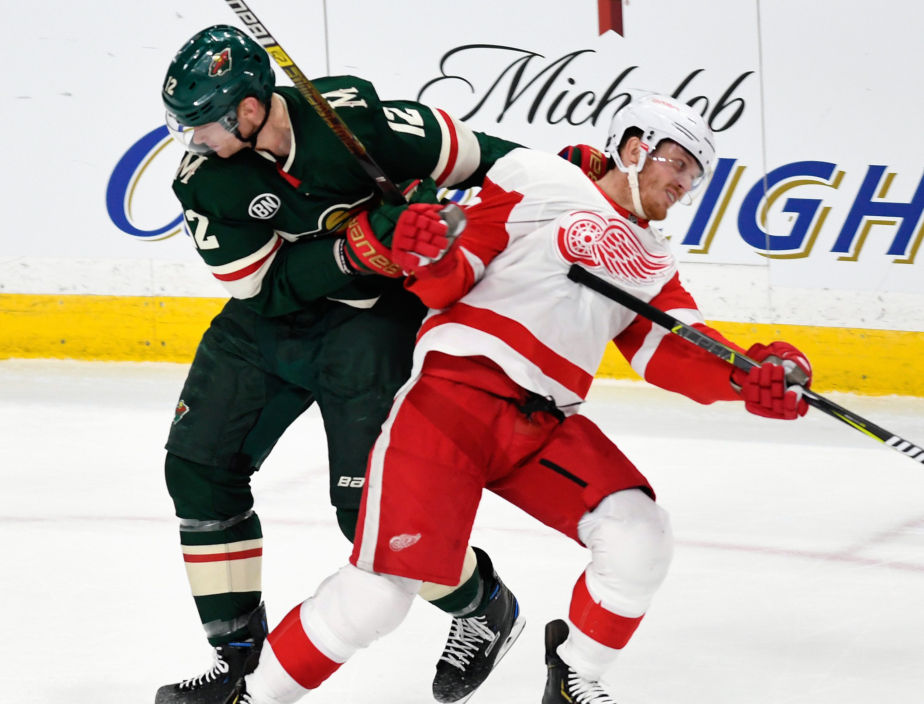 Minnesota Wild's Eric Staal, left, pulls down Detroit Red Wings' Gustav Nyquist, right, of Sweden, during the third period of an NHL hockey game Saturday, Jan. 12, 2019, in St. Paul, Minn. Stall received a penalty for holding on the play. (AP Photo/Tom Olmscheid)