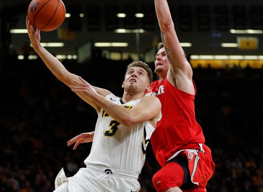 Iowa guard Jordan Bohannon, left, drive to the basket past Ohio State forward Kyle Young, right, during the second half  Saturday. Iowa won 72-62.