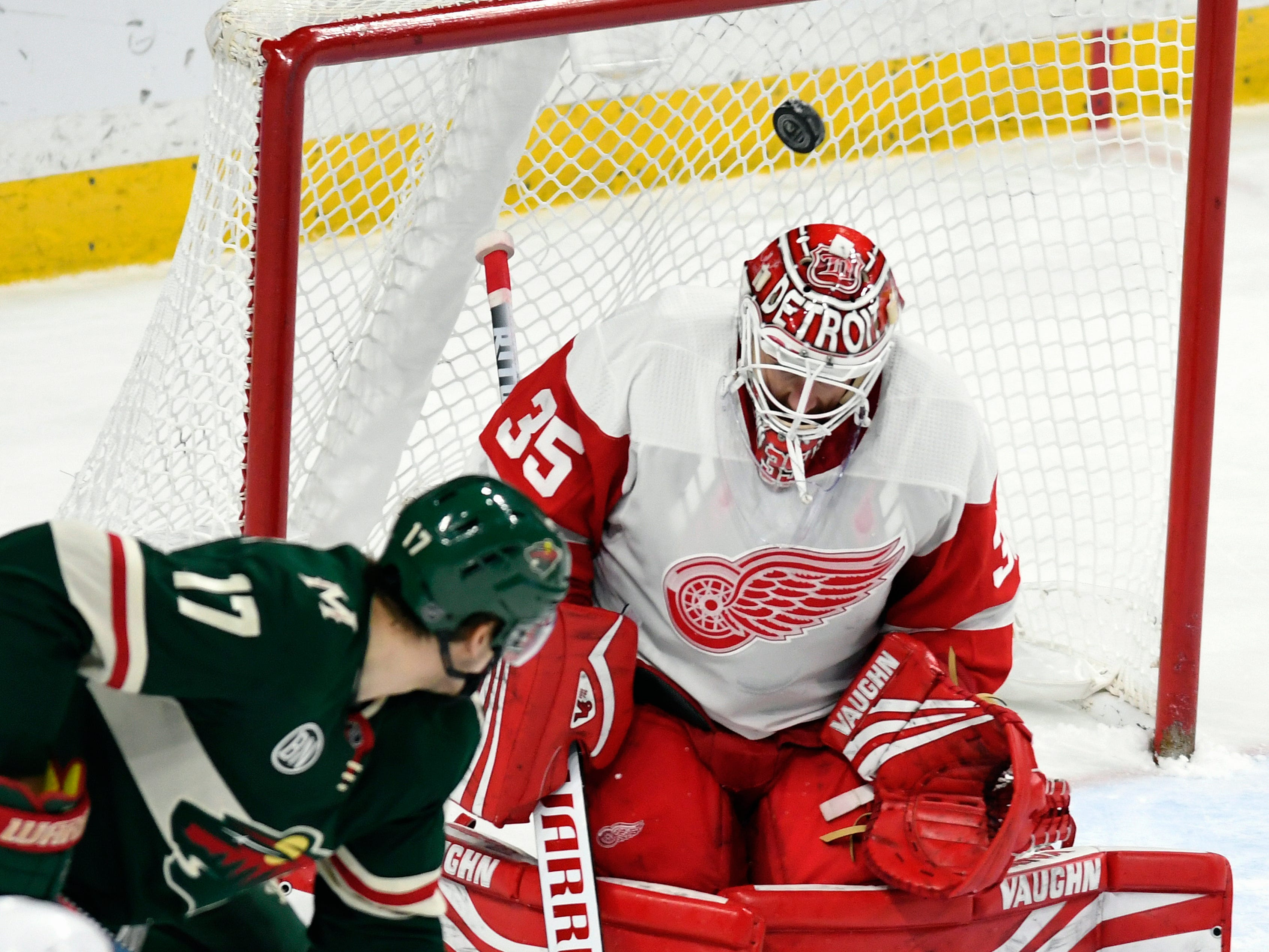 Minnesota Wild's Marcus Foligno (17) tips the puck up over Detroit Red Wings goalie Jimmy Howard during the third period of an NHL hockey game Saturday, Jan. 12, 2019, in St. Paul, Minn. (AP Photo/Tom Olmscheid)
