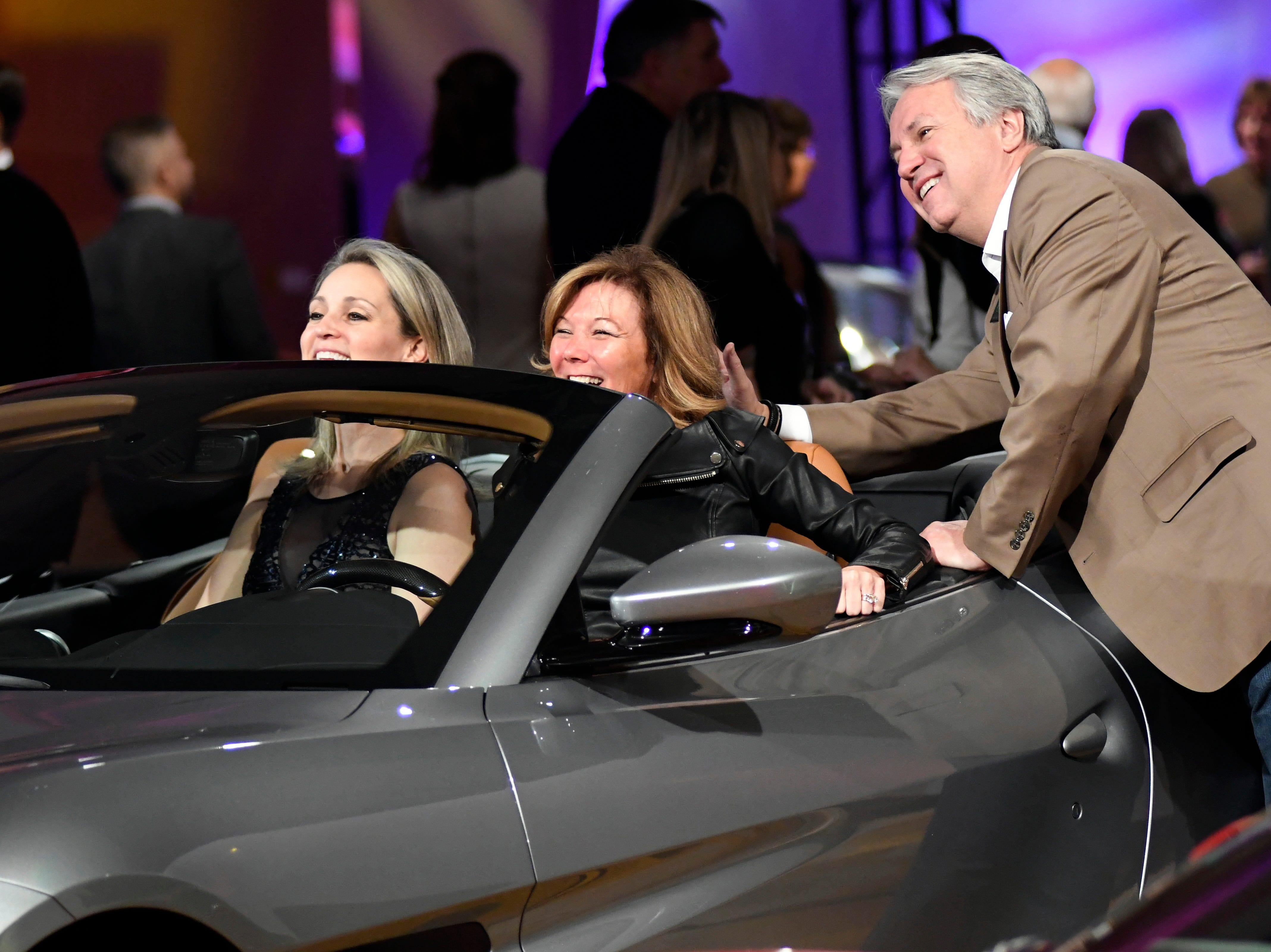 Attendees have fun as they pose for photos inside one of the luxury vehicles at The Gallery.