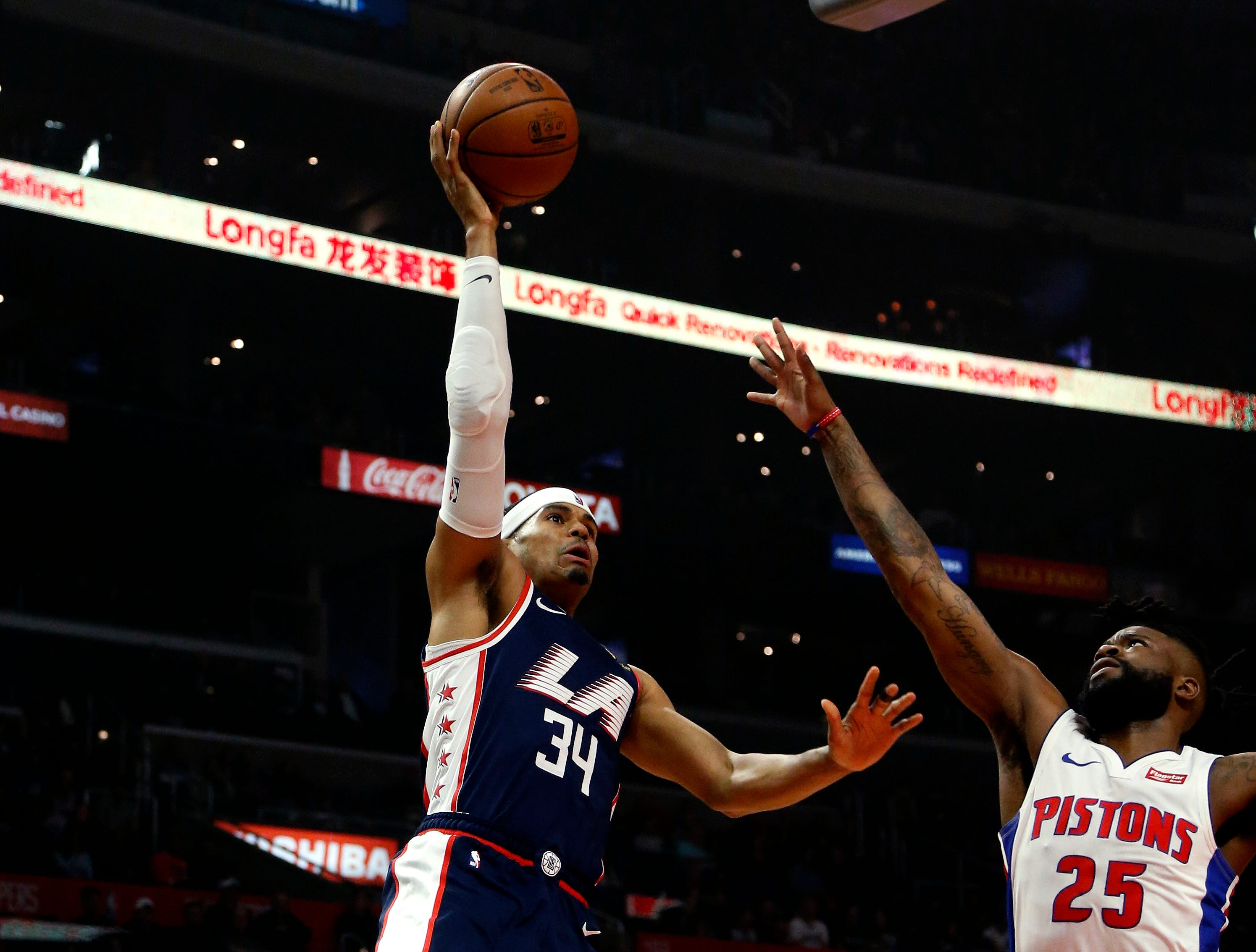 Los Angeles Clippers' Tobias Harris, left, shoots against Detroit Pistons' Reggie Bullock during the first half.
