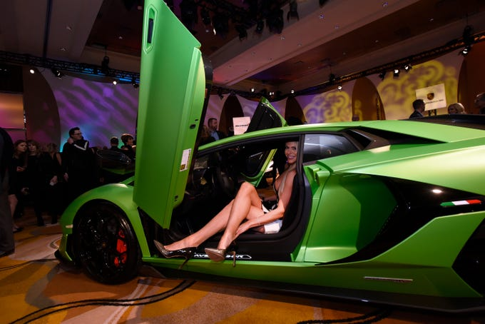 Kimberly Williams of Birmingham takes a seat inside a Lamborghini Aventador and has fun posing for photographers during The Gallery, held at the MGM Grand Detroit, Saturday night, Jan. 12, 2019.  The luxury car event is considered the kick-off to the North American International Auto Show.