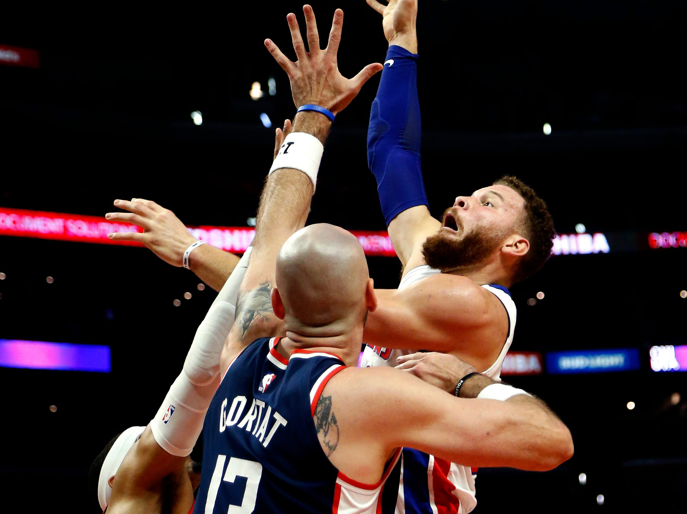 Detroit Pistons' Blake Griffin, right, shoots over Los Angeles Clippers' Montrezl Harrell, left, and Marcin Gortat (13) during the second half.