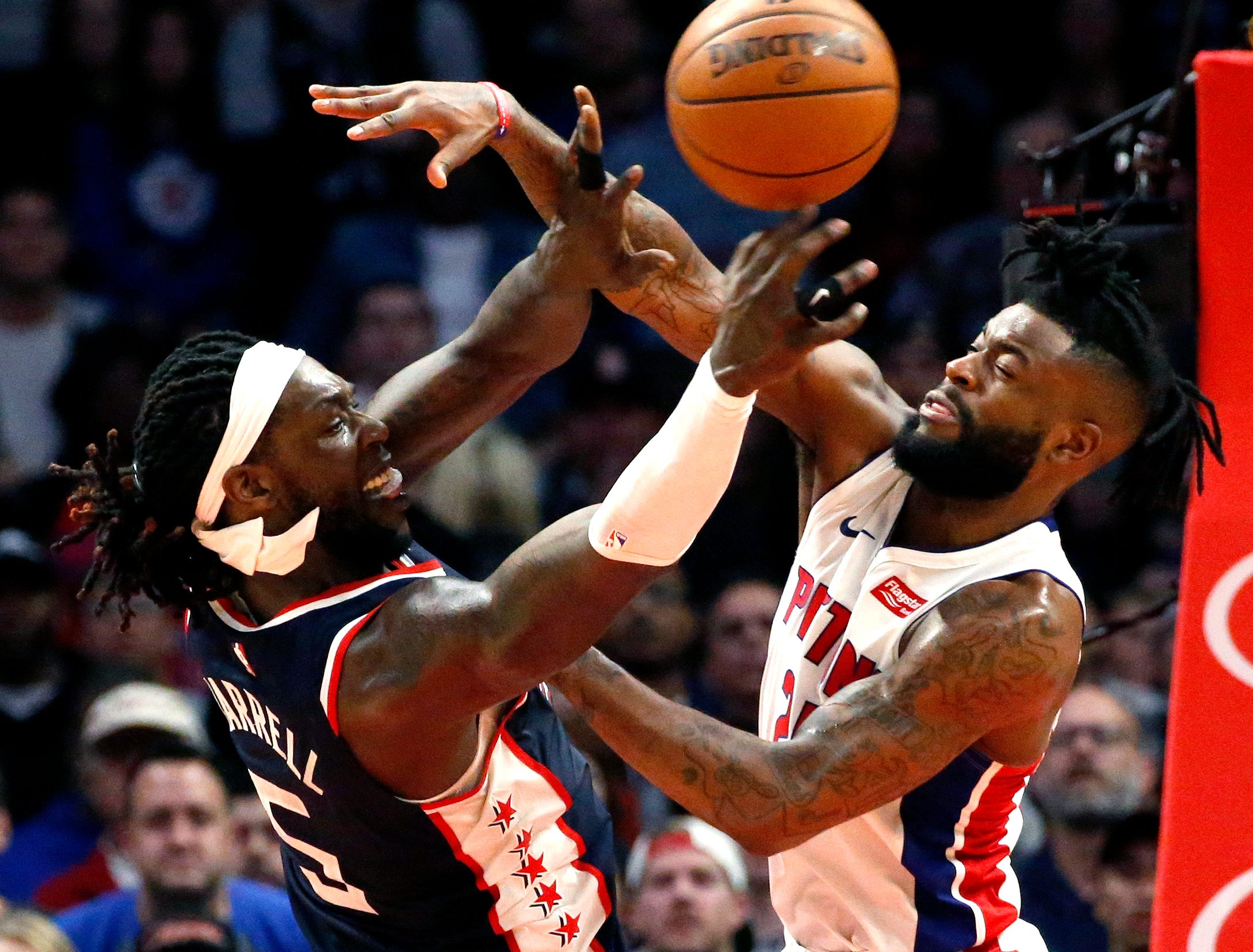 Los Angeles Clippers' Montrezl Harrell, left, passes the ball while defended by Detroit Pistons' Reggie Bullock during the second half.