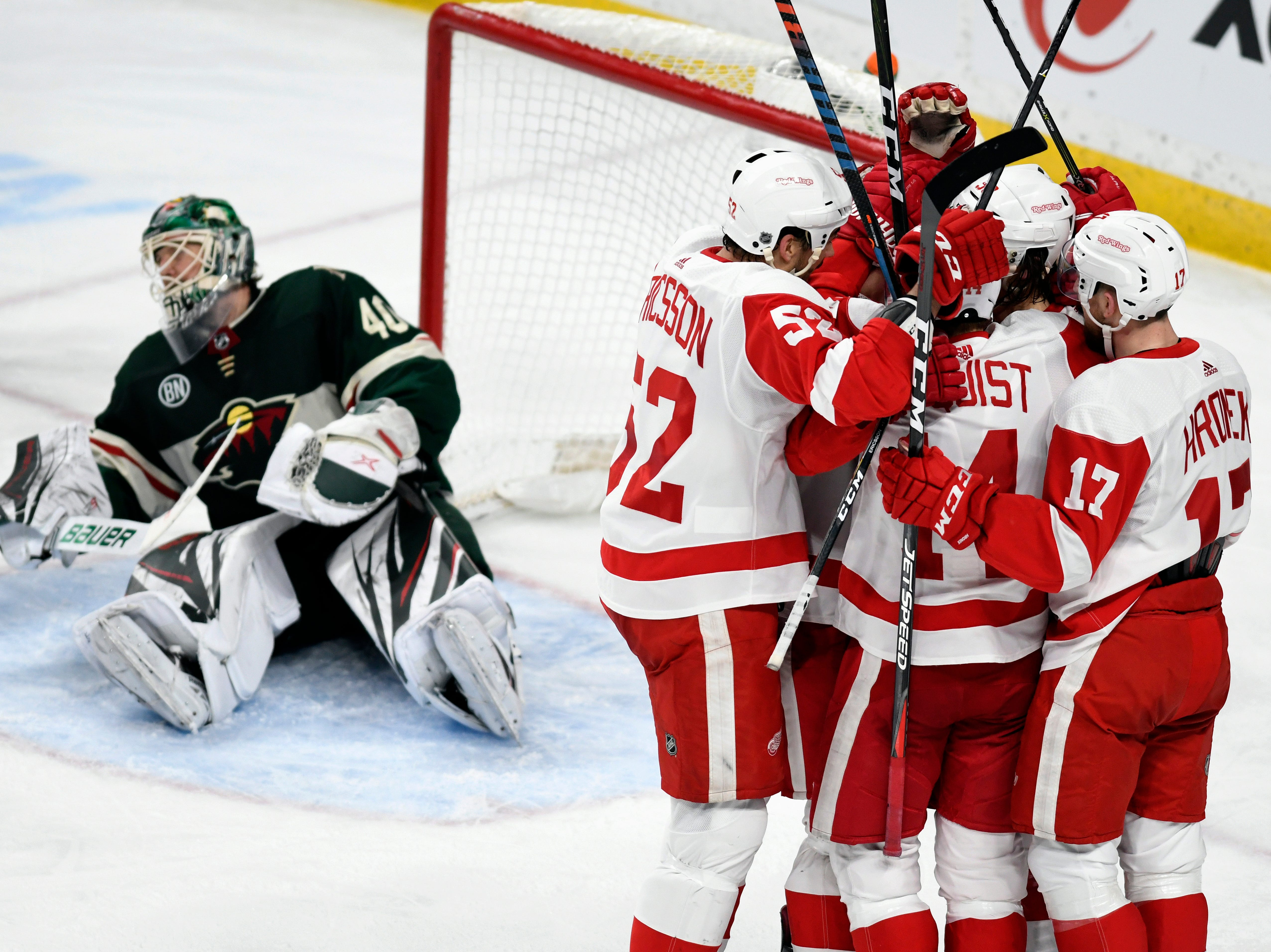 Detroit Red Wings mob teammate Tyler Bertuzzi after he scored his third goal of the game for a hat trick, while Minnesota Wild goalie Devan Dubnyk, left, looks away during the third period of an NHL hockey game Saturday, Jan. 12, 2019, in St. Paul, Minn. (AP Photo/Tom Olmscheid)