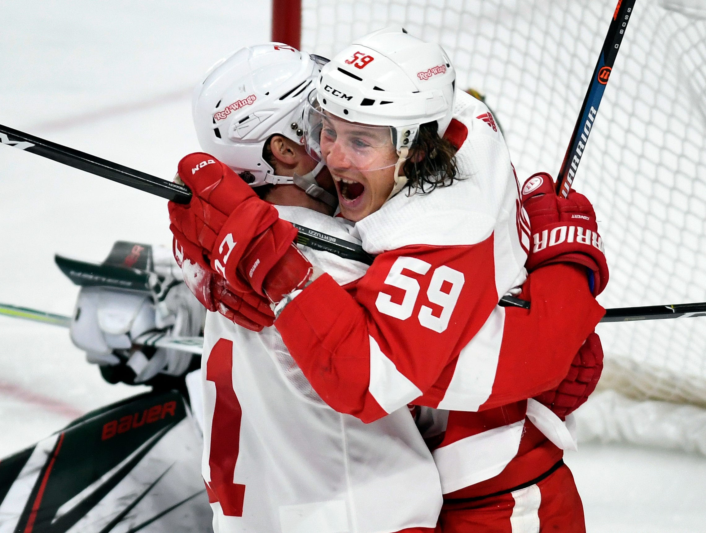 Detroit Red Wings' Dylan Larkin, left, hugs Tyler Bertuzzi (59) after he scored his third goal against the Minnesota Wild for a hat trick during the third period of an NHL hockey game Saturday, Jan. 12, 2019, in St. Paul, Minn. (AP Photo/Tom Olmscheid)