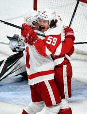 Detroit Red Wings' Dylan Larkin, left, hugs Tyler Bertuzzi (59) after he scored his third goal against the Minnesota Wild for a hat trick during the third period  Saturday. The Red Wings won 5-2.
